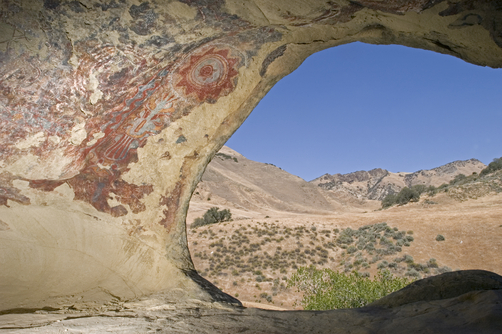 Abstract Chumash pictographs above a cave entrance.